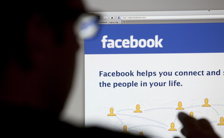 Bath, United Kingdom - May 4, 2011: Close-up of the Facebook homepage displayed on a LCD computer screen with silhouette of a man's head and hand out of focus in the foreground.
