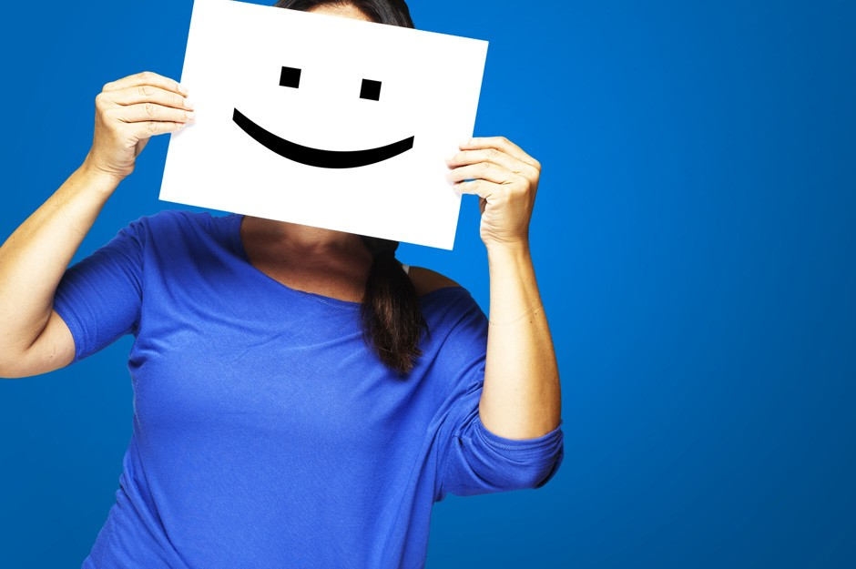 Woman showing a happy emoticon in front of face against a blue background